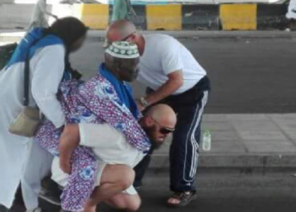 حاج أوروبي يحمل مسنا أفريقيا على ظهره في مكة المكرمة