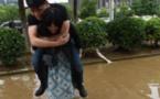 صور صينية تحمل خطيبها على ظهرها لعبور مياه الفيضان